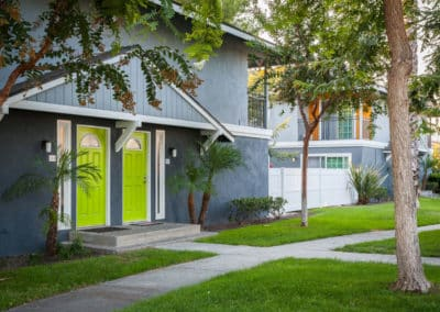 Grassy with tall trees walk ways at Pacific Palms Apartment Homes