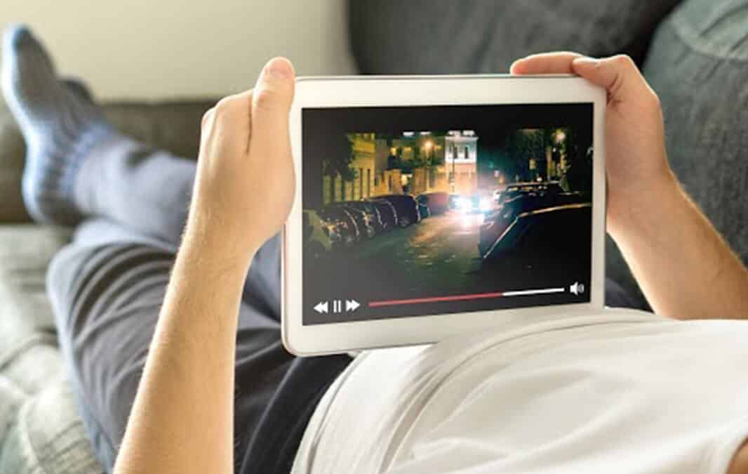 person holding a tablet watching a movie while lying down